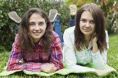 Female friendship 5. Two beautiful college students friends together. Two beautiful girls in the park lie on the grass and looking Royalty Free Stock Photo