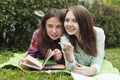 Female friendship1. Two teen girls in the Park lie on the grass with notebooks and look at someone and laugh. School girl. Female friendship. Fun Stock Images