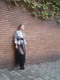 Female in front of brick wall in inner courtyard. Teen female model wearing designer clothing stands leaning against red brick wall Royalty Free Stock Images