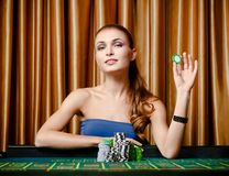 Female gambler with chip in hand at the casino Royalty Free Stock Photo