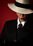 Female gangster. With hat lookin down on the floor royalty free stock photos