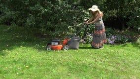 Female garden worker cutting lawn near flower beds and fruit trees. 4K. Female garden worker in dress cutting lawn grass with mower near flower beds and fruit stock video