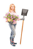 Female gardener holding flowers and a shovel Royalty Free Stock Photos