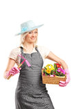 Female gardener holding a mattock and basket Royalty Free Stock Image