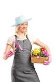 Female gardener holding a mattock and basket Royalty Free Stock Image