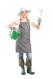 Female gardener holding mattock and watering can Stock Photo