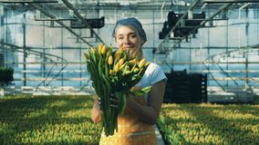 Female gardener holds a bouquet with tulips and smiles at a camera.