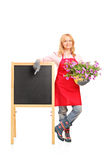 Female gardener standing next to black table and holding flowers Royalty Free Stock Photo