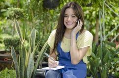 Female gardener taking an order. Cute female gardener taking an order from a customer on the phone Royalty Free Stock Photos