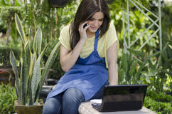 Female gardener taking an order. Cute female gardener taking a note from a customer on the phone Stock Photos