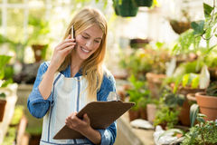 Female gardener talking on cellphone while looking at clipboard Stock Photography