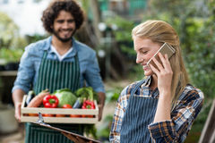 Female gardener talking on cellphone while man in background Royalty Free Stock Photos