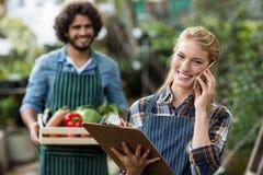 Female gardener talking on mobile phone while man standing Stock Images