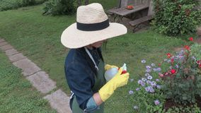 Female gardener try to fix spraying bottle. In summer day stock footage