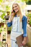 Female gardener using cellphone at greenhouse Royalty Free Stock Photography