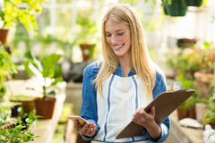 Female gardener using cellphone while holding clipboard Stock Images