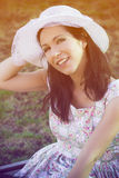 Female gardener with white hat in a garden in the sun Stock Photography
