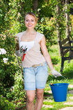 Female gardener with working tools outdoors Royalty Free Stock Photo