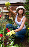 Female Gardening. Young female in gloves and hat working in the garden Royalty Free Stock Photo