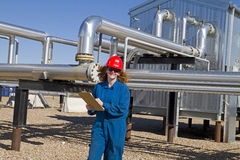 Female gas field operator inspects compressor site Stock Photos