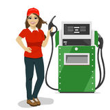 Female gas station worker holding petrol pump standing next to fuel dispenser Royalty Free Stock Images