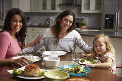 Female gay couple and daughter dining at home look to camera stock photography