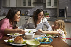 Female gay couple and daughter having dinner in their kitchen Royalty Free Stock Image