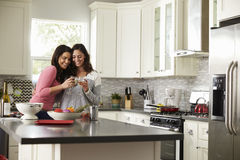 Female gay couple embracing make a toast in the kitchen Stock Images