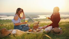 Female gay couple had a picnic. They talking and drink wine. Mid shot stock footage
