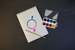 The female gender symbol is equal to the male concept of gender equality. A woman is painting a symbol of gender equality stock images