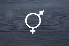 Female gender symbol of equality male, the concept of gender equality. Black wooden background. A paper-cut symbol of gender. Equality. Unique texture. 50/50 stock image