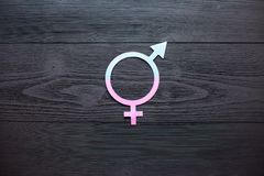 Female gender symbol of equality male, the concept of gender equality. Black wooden background. A paper-cut symbol of gender. Equality. Unique texture. 50/50 stock images