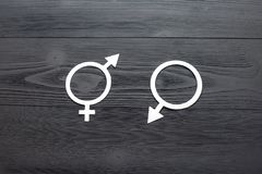 The female gender symbol, gender symbol for men and symbol of gender equality, the concept of gender equality. Black wooden. Background. A paper-cut symbol of royalty free stock image