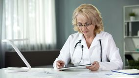 Female general practitioner reading patient's online medical records on tablet stock photos