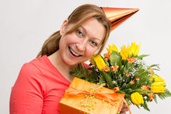 Female with gift. Female holding a present and a bouquet Stock Images