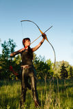 Female ginger hair archer shooting targets with her bow and arrow. Concentration, target, success concept. Copy space text Stock Photos