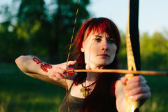 Female ginger hair archer shooting targets with her bow and arrow. Concentration, target, success concept. Copy space text Stock Photography
