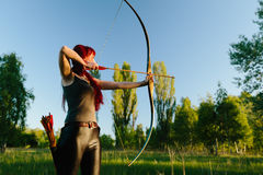 Female ginger hair archer shooting targets with her bow and arrow. Concentration, target, success concept. Copy space text Stock Images