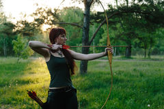 Female ginger hair archer shooting targets with her bow and arrow. Concentration, target, success concept. Royalty Free Stock Image