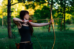 Female ginger hair archer shooting targets with her bow and arrow. Concentration, target, success concept. Copy space text Stock Image
