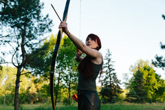 Female ginger hair archer shooting targets with her bow and arrow. Concentration, target, success concept. Copy space text Royalty Free Stock Photos