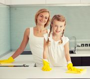 Female with girl cleaning cooker Royalty Free Stock Images