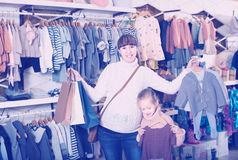 Female and girl enjoying purchases in baby's  cloths store Stock Images