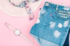 Female girly clothes, blue jeans shorts, hat, watch on pink background. Modern lifestyle stock photography