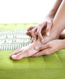Female giving herself foot massage Stock Photos
