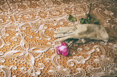 Female glove with a rose. Female glove holding a rose on an elegant table cloth. slight vintage look Royalty Free Stock Photos