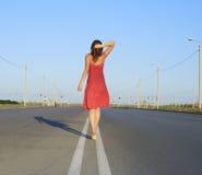 Female go away on empty road Stock Photo