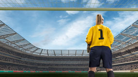 Female goakeeper standiing on goal on crowded stadium royalty free stock image