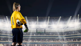 Female goalkeeper standing with the ball against the crowded stadium at night. Female football player in yellow uniform holding ball on full stadium on Royalty Free Stock Image