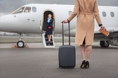 Businesswoman keeping luggage opposite aircraft royalty free stock image